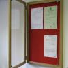 Lockable felt notice board in situ - Single door with wood frame - Cherry